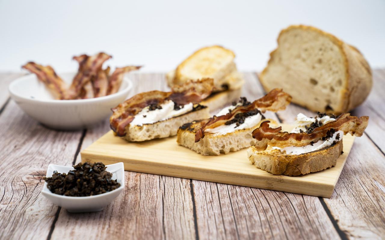 Crostini di pane con mascarpone, pancetta croccante e granella di olive nere